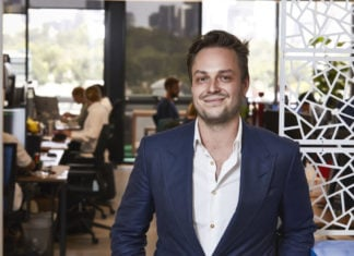 Bitcoin.com.au co-founder Rupert Hackett stands in office.