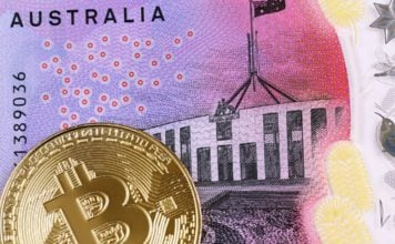 A close up image of a golden bitcoin with an Australian five dollar bill